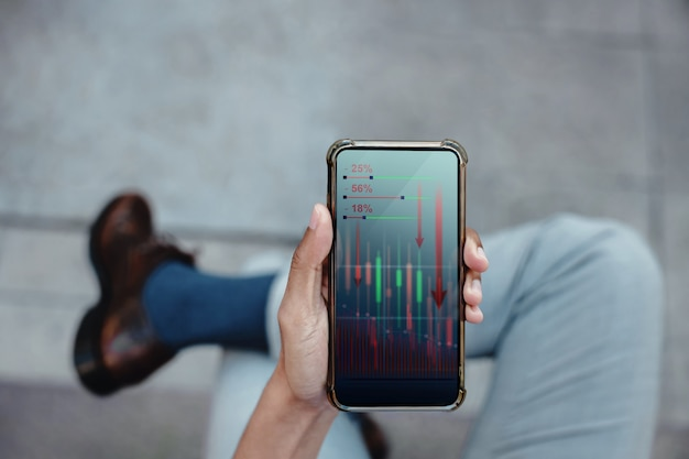 Financial or economy crisis concept. business leader. stock marketing graph is going crash and down. professional businessman seeing low profit graph on mobile phone