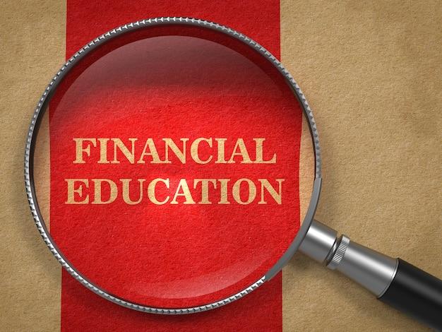 金融教育の概念。赤い縦線の背景を持つ古い紙の虫眼鏡。