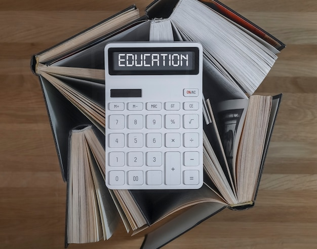 Financial education concept word on calculator with books on accounting and finance