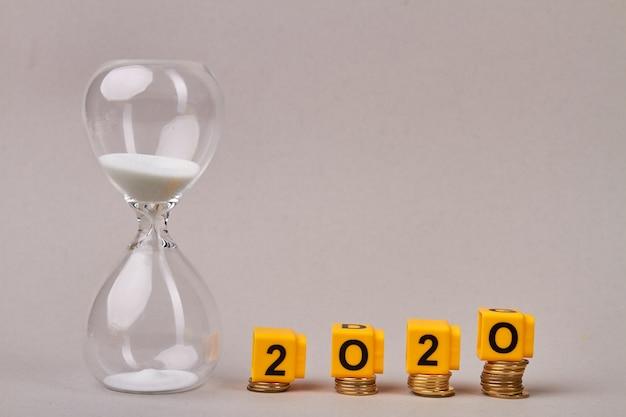 コインの山に砂時計と黄色のブロックがある2020年の財政目標