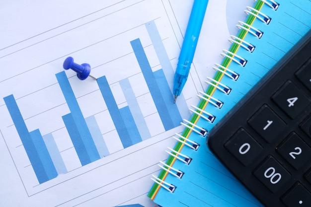 Финансовый график, калькулятор и блокнот на столе
