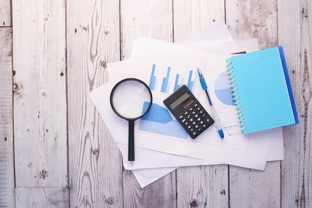 Финансовый график, калькулятор и блокнот на столе.