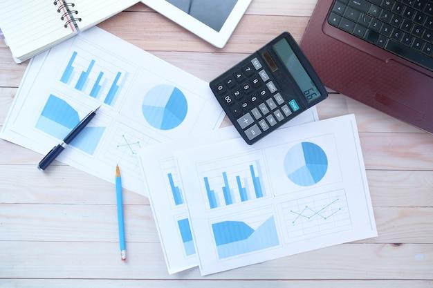 テーブルの上の財務グラフ電卓とメモ帳