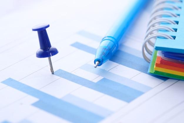 Финансовый график, булавка и блокнот на столе