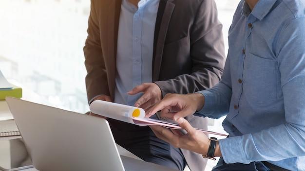 Финансовое изображение двух деловых людей, указывающих на сводный отчет презентации бизнес-документа, во время обсуждения на встрече, записная книжка на деревянном столе