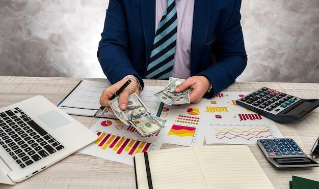 財務検査官は、今年の販売の収入または予算について、グラフ チャート紙とラップトップを使用して財務計画レポートを作成します。