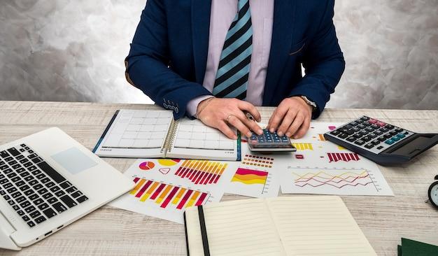 Финансовый инспектор составляет отчет о финансовом планировании с использованием миллиметровой бумаги и ноутбука для доходов или бюджета продаж в этом году.