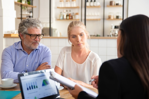 Agente di assicurazione finanziaria che incontra clienti giovani e maturi in coworking, mostra accordo e spiega i dettagli