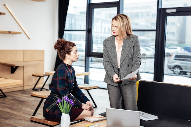 Financial issues. blonde-haired businesswoman explaining some financial issues to her young partner