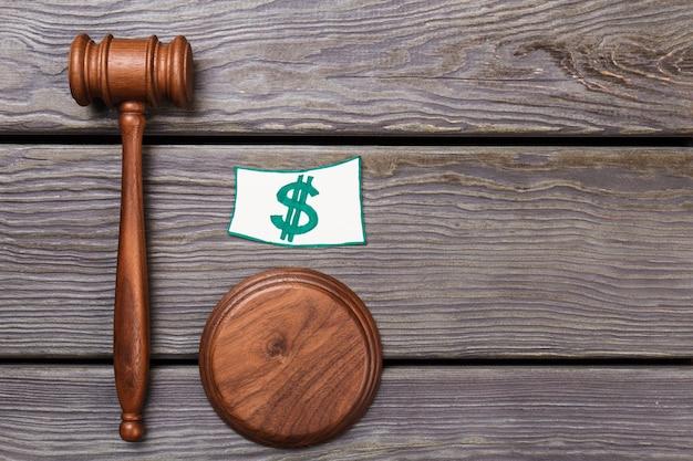 Концепция финансовой справедливости. деревянный молоток правосудия и знак доллара. молоток вида сверху на столе.