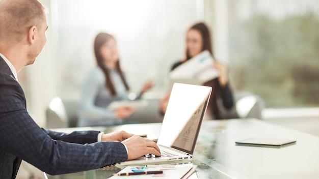 財務データを使用してラップトップに取り組んでいる財務マネージャー