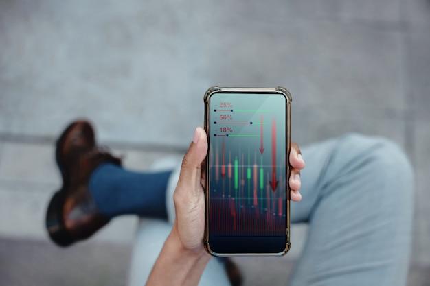 金融または経済危機の概念。ビジネスリーダー。株式マーケティンググラフがクラッシュしてダウンしています。携帯電話で低利益グラフを見てプロのビジネスマン