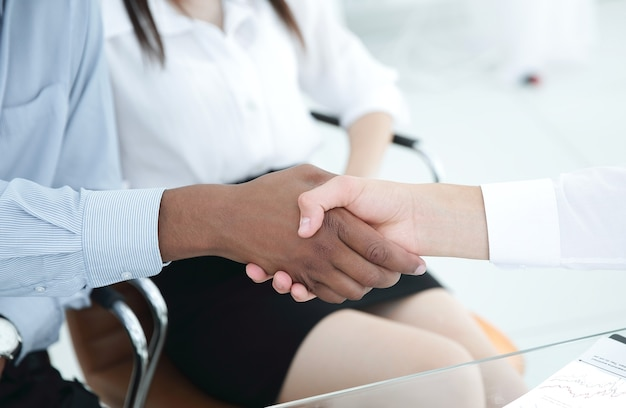 Financial partners shaking hands over a desk