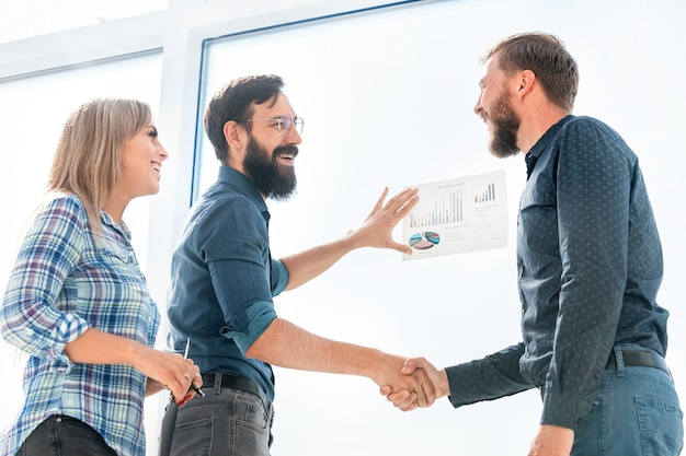 Финансовые партнеры, пожимая руки стоя в офисе. бизнес-концепция