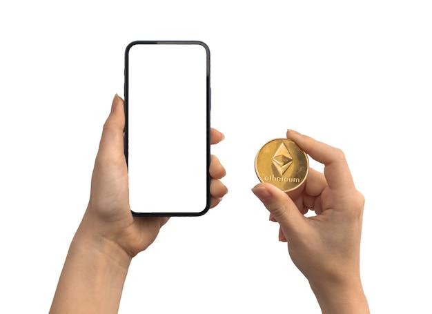 Финансовые платежи с помощью эфириума eth и мобильного телефона, пустой белый макет экрана, руки с монетой криптовалюты, изолированные на белом фоне фото