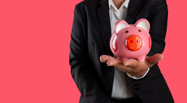 Financial planning, business person holding piggy bank in hand isolated on magenta pink.