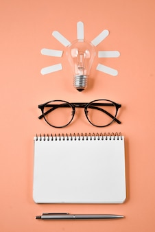 Financial planning table top with pen, notepad, eyeglasses and light bulb on orange background.