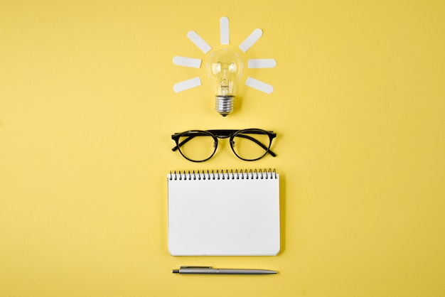 Financial planning table top with pen, notepad, eyeglasses and light bulb on yellow background.