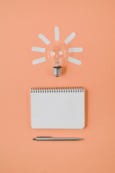 Financial planning table top with pen, notepad, light bulb on orange background.