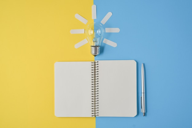 Financial planning table top with pen, notepad, light bulb on yellow and blue background.