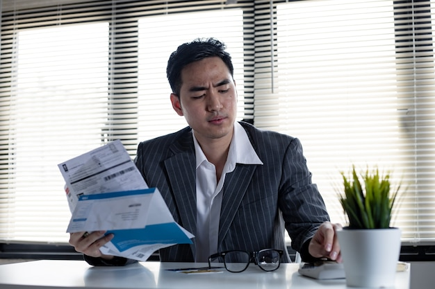 財政問題の概念。男は電卓で手元の借金を計算します。若いアジア人男性は、多くのクレジットカードや請求書からの借金によってストレスを感じ、考えすぎています。