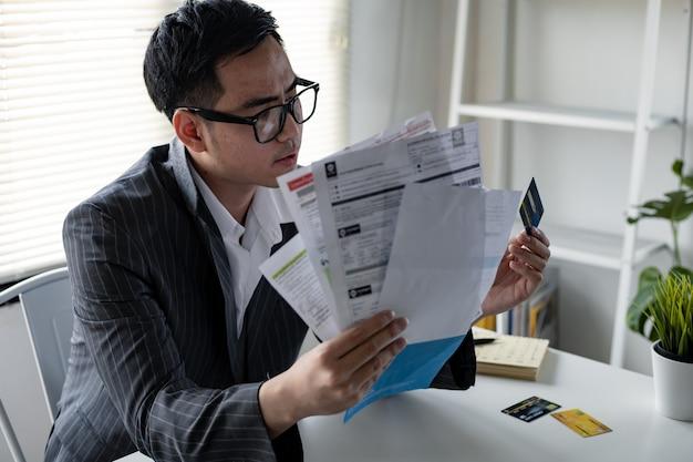 財政問題の概念。若いアジア人男性は、多くのクレジットカードや請求書からの借金によってストレスを感じ、考えすぎています。男は手元の借金から抜け出す方法を考え出した。