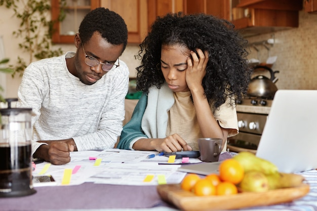 Financial problem and economic crisis concept. angryafrican male in glasses having stressed and puzzled expression, thinking over numerous debts, his unhappy wife sitting next to him and crying