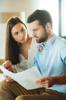 Financial problems. frustrated young man holding papers and looking at them while woman sitting close to him and pointing document