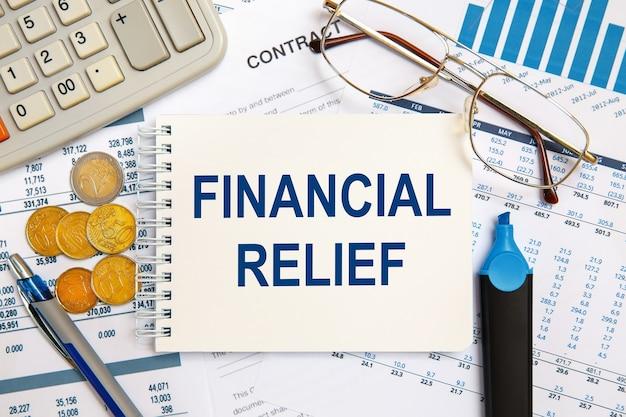 재정 구호는 사무실 액세서리와 함께 사무실 책상에 메모장에 기록됩니다.