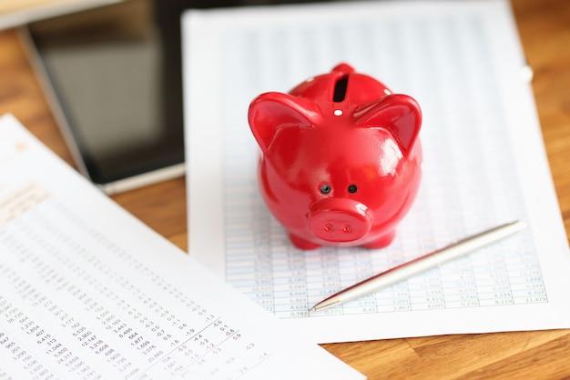 財務報告と赤豚の貯金箱がテーブルにあります