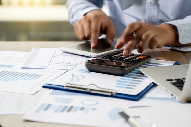 Financial report- business accounting money stack concept business man using calculator graph discussion and analysis data charts and graphs