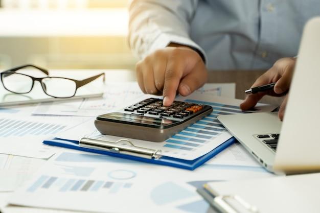 財務報告-ビジネス会計マネースタックコンセプトビジネス男電卓を使用してグラフのディスカッションと分析データのチャートとグラフ