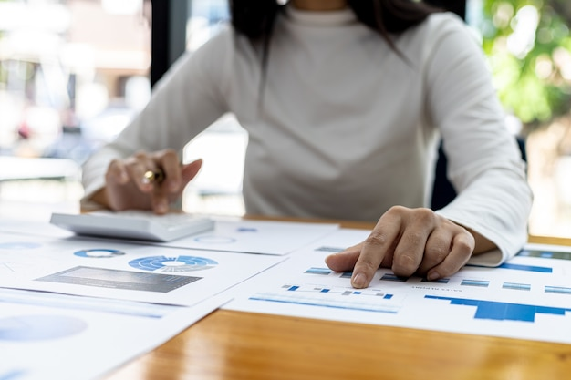 A financial scholar is pointing at a document with a pen, she is analyzing and checking company financial data for accuracy before presenting it to the meeting. financial audit concept.