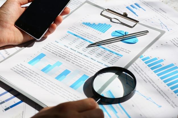 手のクローズアップでスマートフォンを保持している金融統計。