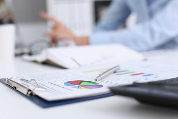 Financial statistics documents on clipboard pad