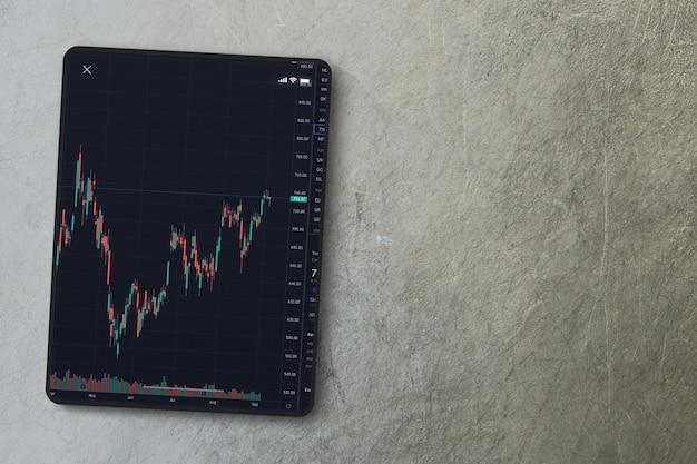 시멘트 배경에 태블릿 화면에 금융 주식 시장 그래프. 평면도. 증권 거래소.