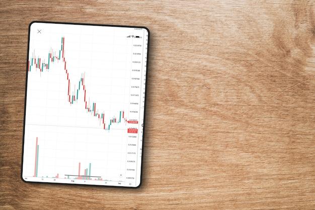 나무 배경에 태블릿 화면에 금융 주식 시장 그래프. 평면도. 증권 거래소.
