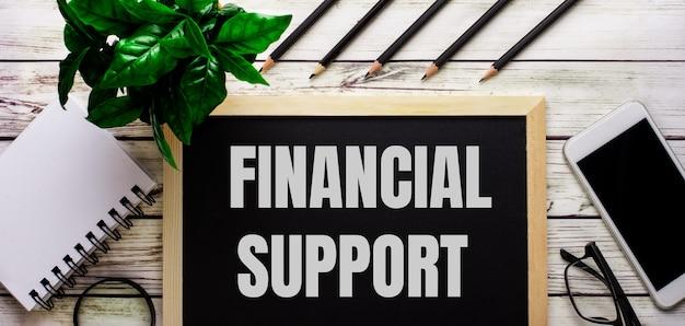 Финансовая поддержка написана белым на черной доске рядом с телефоном, блокнотом, очками, карандашами и зеленым растением.