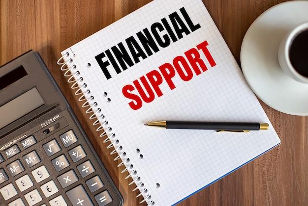 電卓の近くの白いメモ帳と暗い木の表面に一杯のコーヒーで書かれた財政支援