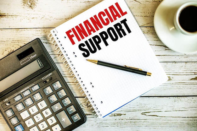 Financial support written on white paper near coffee and calculator on a light wooden table. business concept