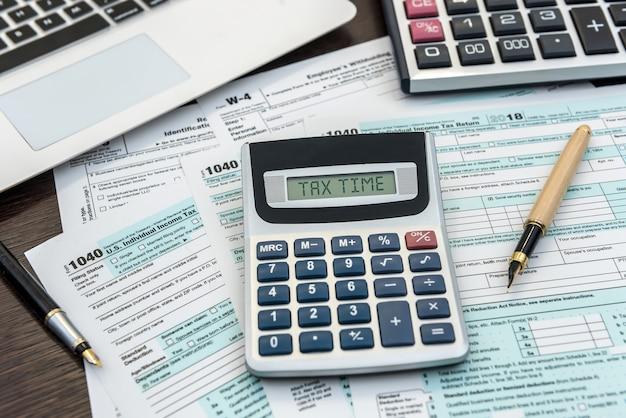 ノートパソコンと電卓を備えた金融時間税フォーム。オフィスの事務処理。会計