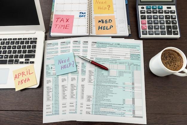ノートパソコンと電卓を備えたフィナンシャルタイム納税申告書
