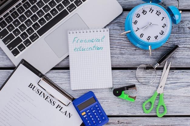 Финансовое образование и концепция бизнес-плана. калькулятор с ноутбуком и часами на белом деревянном столе.