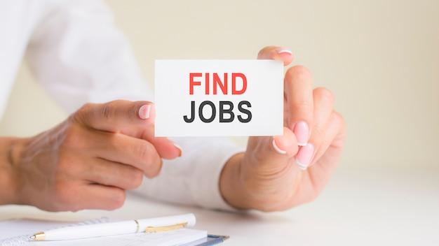 女性の手で白いカードの紙のシートに仕事の単語の碑文を見つけます。白い紙に黒と赤の文字。ビジネスコンセプト、灰色の背景、ペンと