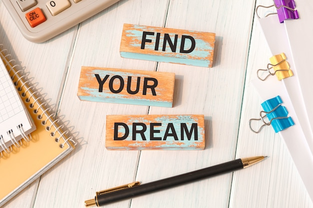 事務用品の近くの木のブロックに書かれたあなたの夢の言葉を見つけてください