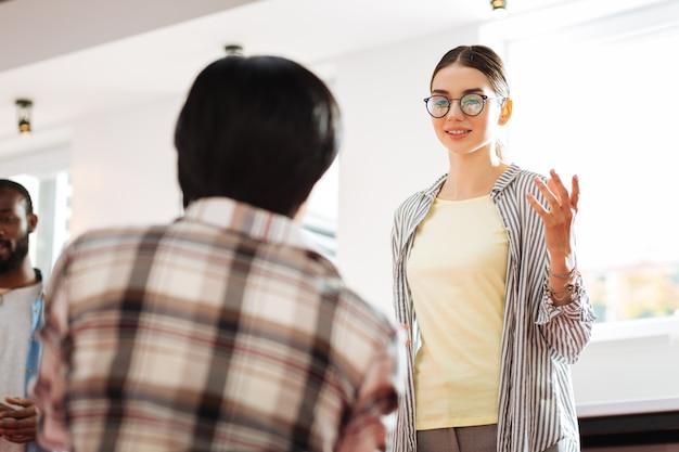 영감 찾기. 쾌활한 성공적인 젊은 여성이 그녀의 개인적인 성장에 대해 이야기하고 젊은 전문가에게 희망을주는