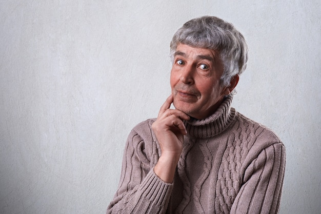 Finding perfect solution. mature handsome man with gray hair and wrinkles holding his finger on cheek looking thoughtful