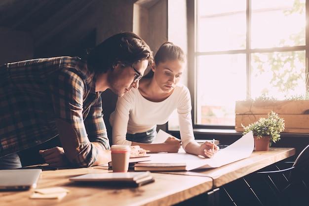 함께 해결책을 찾습니다. 캐주얼 차림의 자신감 있는 젊은 남성과 여성이 함께 청사진을 바라보며 창의적인 사무실의 나무 책상 근처에 서 있는 동안