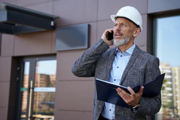 Поиск решений серьезный зрелый инженер-архитектор, менеджер в шлеме, глядя в сторону, разговаривает