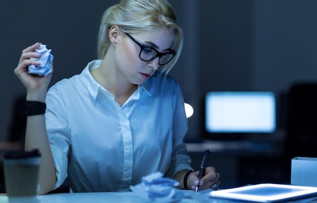 최선의 탈출구 찾기. 사무실에 앉아서 태블릿을 사용하면서 프로젝트를 진행하고 메모를하는 목적이있는 젊은 it 여성